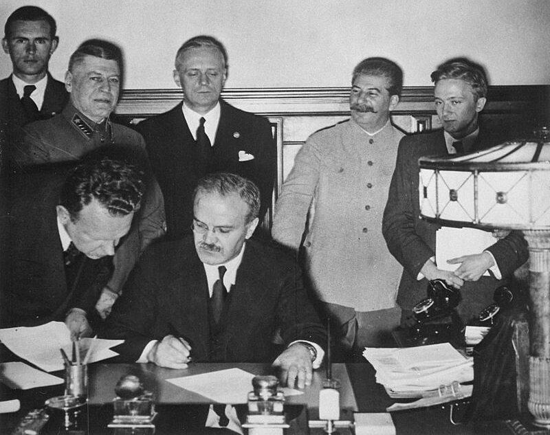 Wiaczesław Mołotow podpisuje radziecko-niemiecki Pakt o Nieagresji, 23 sierpnia 1939 roku. Z tyłu stoi Joachim von Ribbentrop i uśmiechnięty Józef Stalin